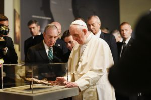 NEW YORK, NY - SEPTEMBER 25: Pope Francis walks in the Historic Exhibiion hall of the 911 Museum Memorial with dignitaries including Cardinal Timothy Dolan and Former New York City Mayor, Michael Bloomberg and looks at a New Testament bible fragment found in debris of the South Tower on September 25, 2015 in New York City. Pope Francis is on a six-day trip to the United States, which includes stops in Washington DC, New York and Philadelphia. (Photo by Carmine Galasso-Pool/Getty Images)